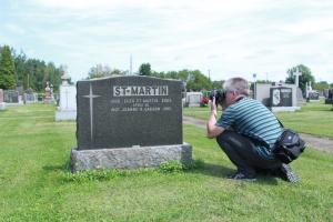 Eric Veillette photographiant l'épitaphe de Marie-Jeanne Gagnon, la sœur de la célèbre Aurore Gagnon, dans le cimetière St-Joseph de Shawinigan.
