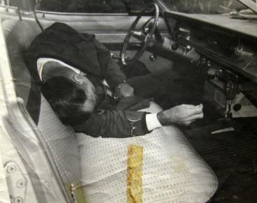 Photographie C-20-D, le corps du policier Louis-Georges Dupont tel qu'il a été retrouvé dans sa voiture de service le 10 novembre 1969. L'enquête a conclu qu'il s'agissait d'un suicide.